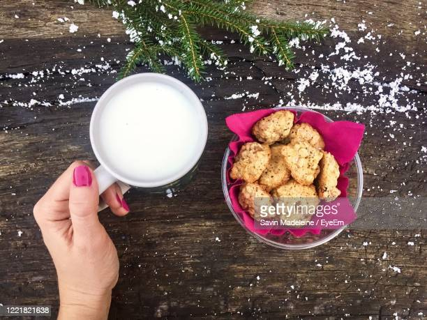 woman hand holding a mug of milk with cookies beside on wooden table powdered with snow - lady madeleine stock-fotos und bilder