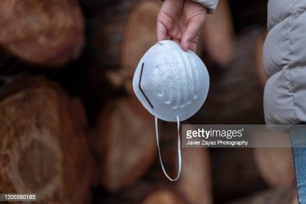 woman hand holding an allergy mask - coronavirus stockfoto's en -beelden