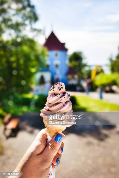 Woman hand holding chocolate ice cream cone