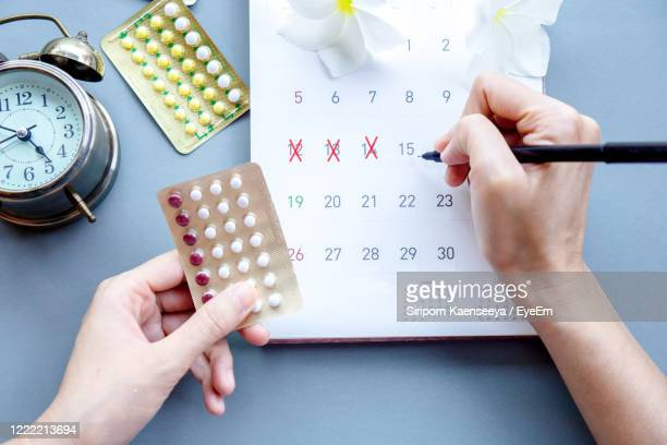 woman hand holding contraceptive pills and mark the date on calendar - 検査業務 開始の地 ストックフォトと画像