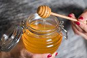 Woman hand holding glass jar of honey