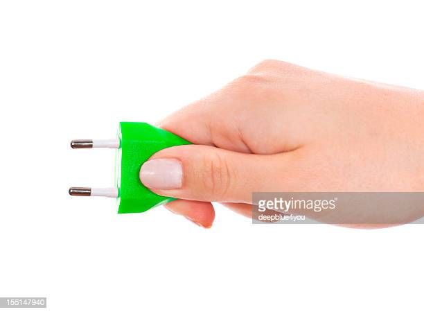 Woman hand holding green plug isolated on white