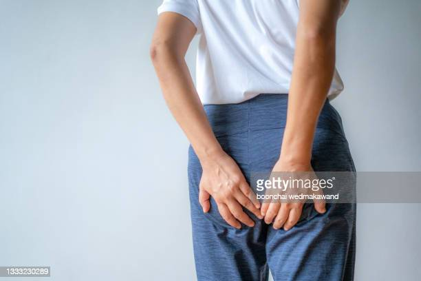 woman hand holding her bottom because having abdominal pain and hemorrhoids, health care concept. - オナラ ストックフォトと画像