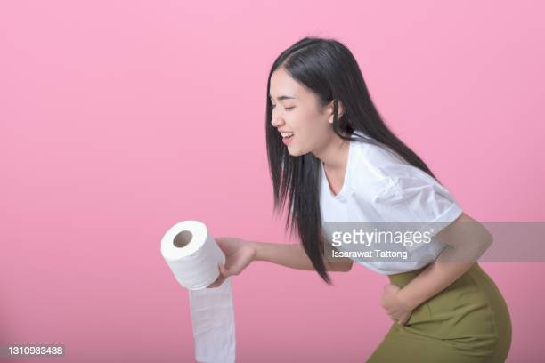 woman hand holding her crotch lower abdomen and tissue or toilet paper roll. disorder, diarrhea, incontinence. healthcare concept. - hemorrhoids stock pictures, royalty-free photos & images