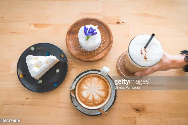 woman hand holding Ice coffee, hot coffee and cake on the wooden table in the coffee cafe.