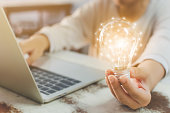 Woman hand holding light bulb and using laptop on wooden desk. Concept new idea with innovation and creativity