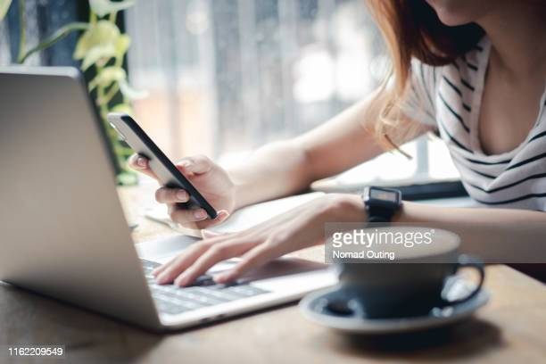 woman hand holding mobile phone and using laptop computer on cafe. - social media marketing stock pictures, royalty-free photos & images