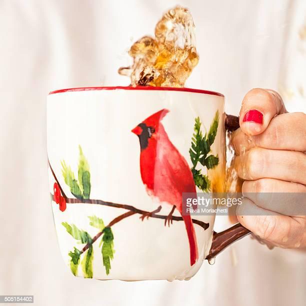 Woman hand holding mug with tea splashing
