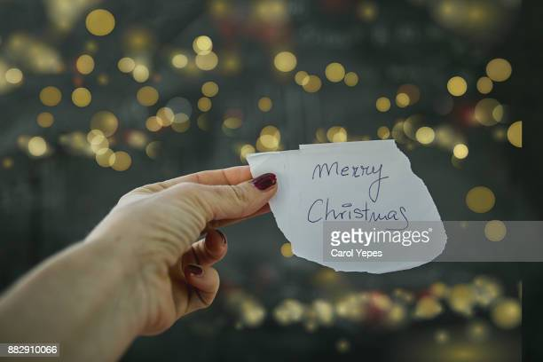 woman hand holding paper with merry christmas message