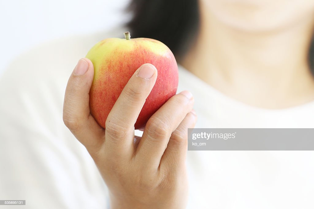 Woman hand holding red apple. : Stock Photo