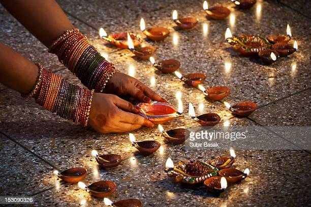 Woman hand lighting divas at Diwali.