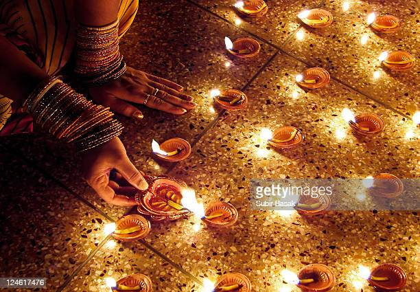 woman hand lighting diva's - diwali celebration stock photos and pictures