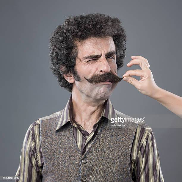 Woman Hand Pulling Up Adult Man's Handlebar Moustache