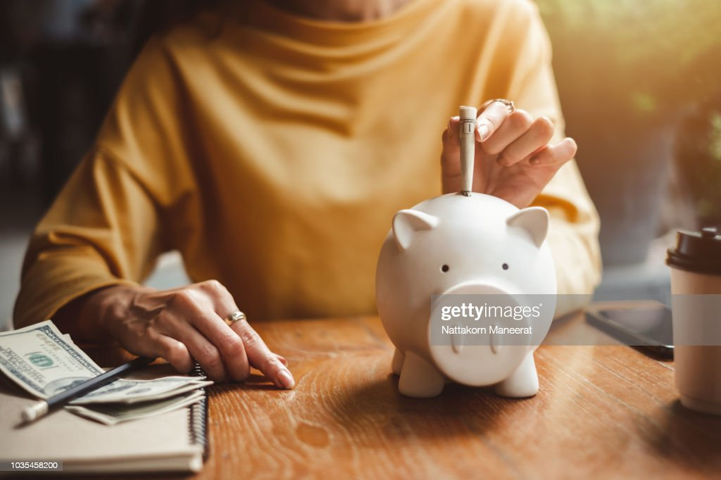 woman hand putting money bank note dollar into piggy for saving money wealth and financial concept. : Stock Photo