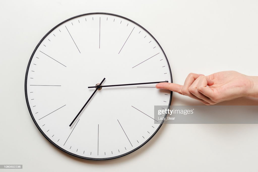 Woman hand stop time on round clock, female finger takes the minute arrow of the clock back, time management and deadline concept : Stock Photo