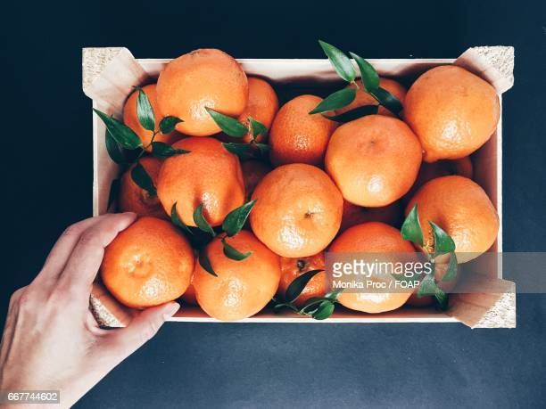 Woman hand taking orange from fruit basket