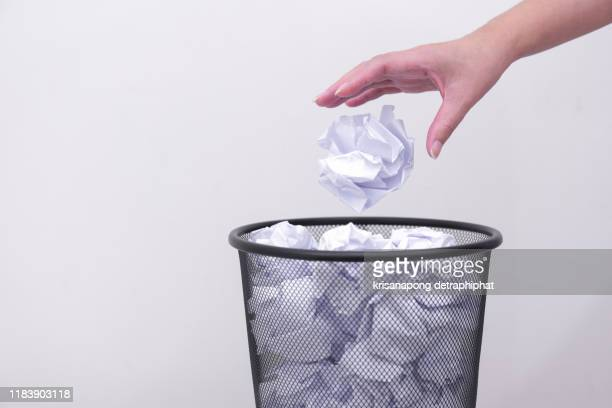 woman hand throwing crumpled paper in basket,littering, trash - the_writer's_block stock pictures, royalty-free photos & images