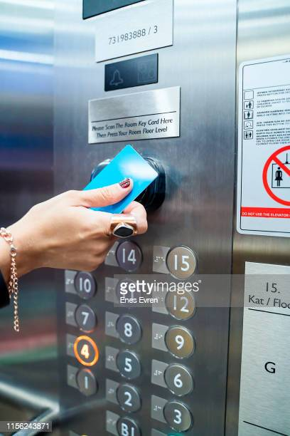 Woman hand touching by hotel check-in card to elevator button