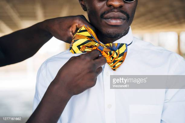 woman hand tying traditional bow tie on man shirt while standing in building - bow tie stock pictures, royalty-free photos & images