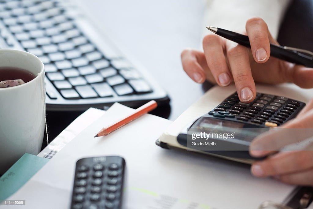 Woman hand using calculator : Stock Photo