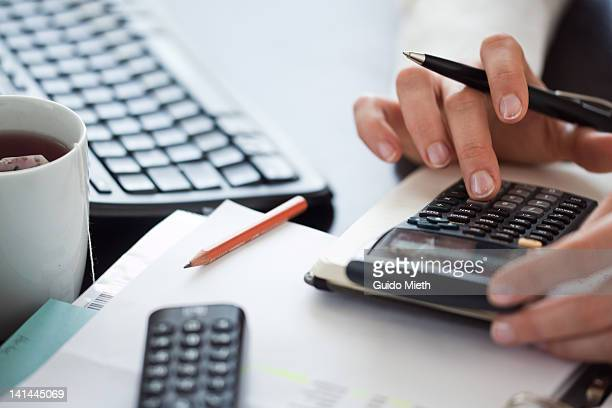 woman hand using calculator - calculator stock photos and pictures