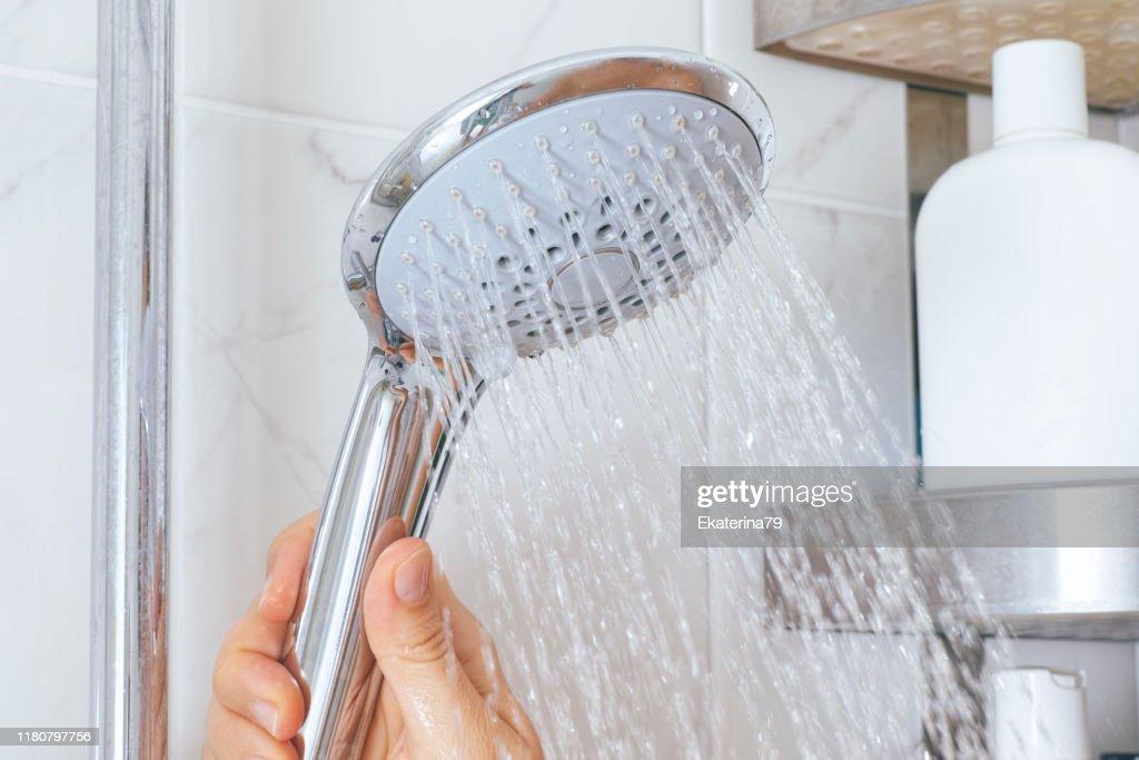 Woman hand using shower head in bathroom. : Stock Photo