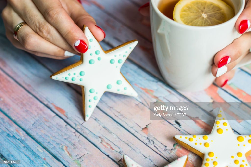 Woman hand with cup of tea and cookie : Stock Photo