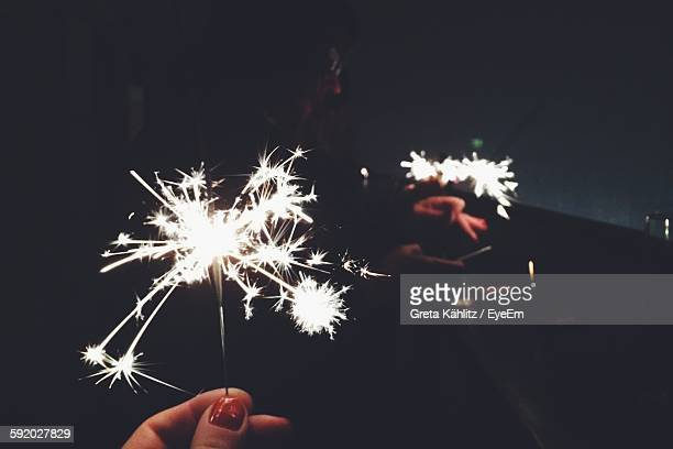 Woman Hand With Fireworks At Night