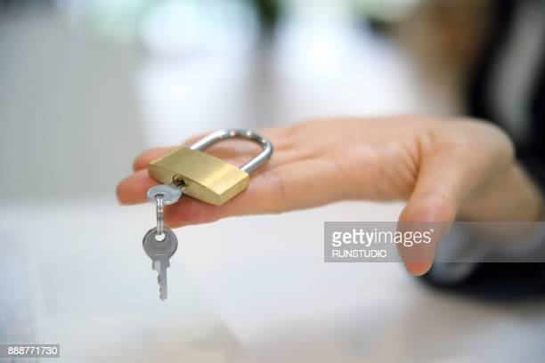 Woman hand with padlock and key