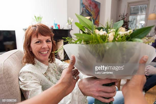 woman handing a bunch of flowers to the viewer - lucy lambriex stockfoto's en -beelden