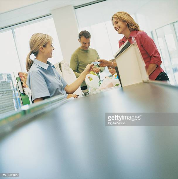 Woman Handing a Cashier Her Bank Card at a Supermarket Checkout Counter