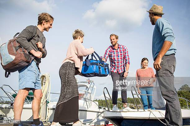 Woman handing bag to friend on yacht
