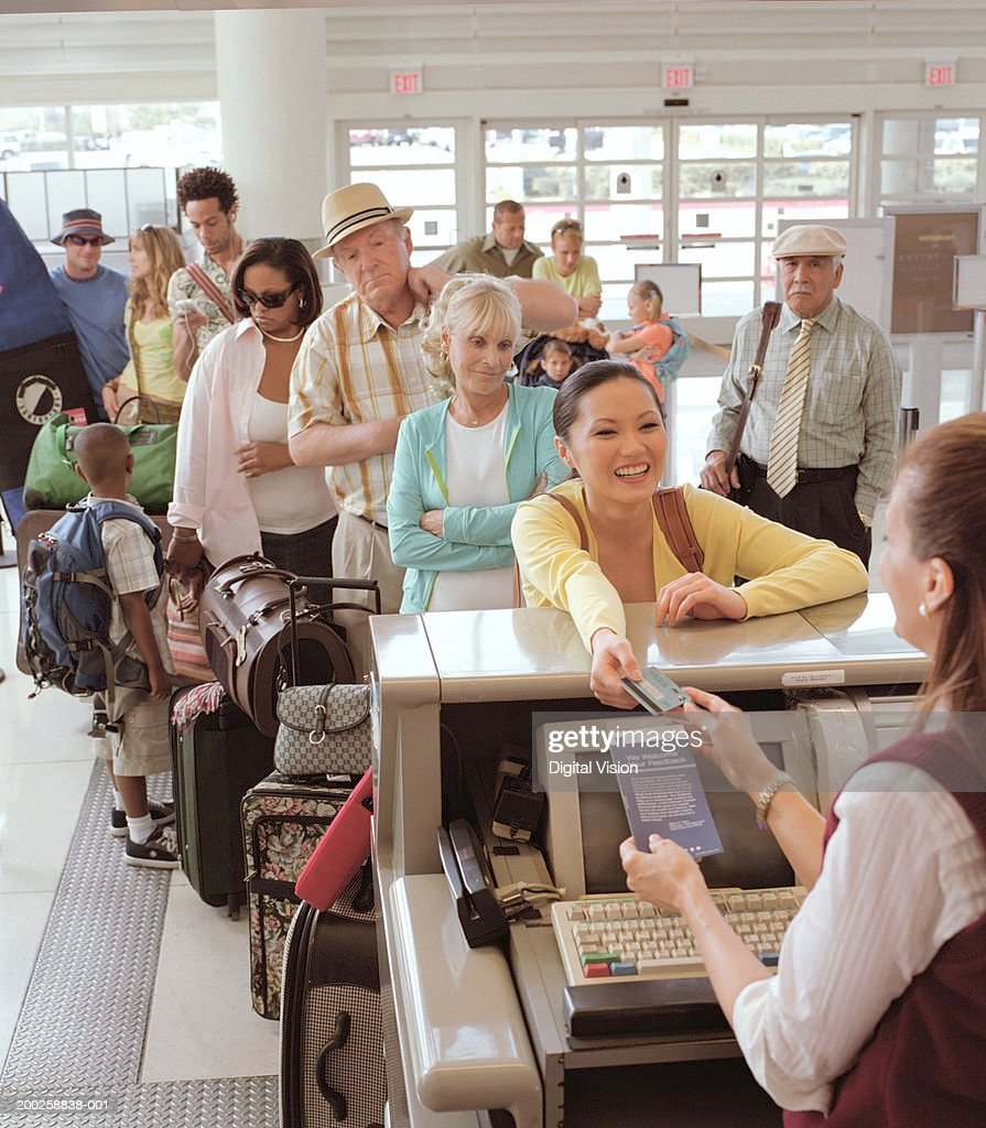 Woman handing bank card to woman at airport check in desk, smiling : Stock Photo