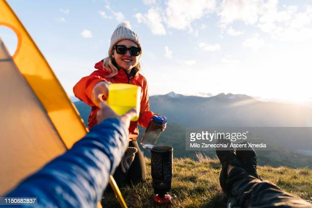 pov of woman handing beverage to camera, view of valley at sunset next to tent - subjektive kamera ungewöhnliche ansicht stock-fotos und bilder