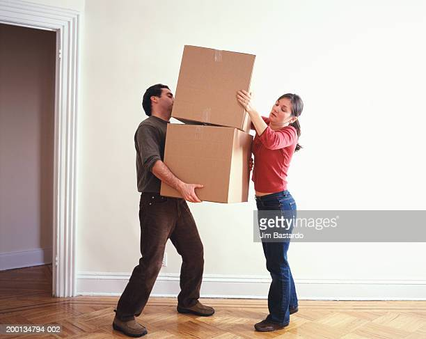 Woman handing box to man in bare room