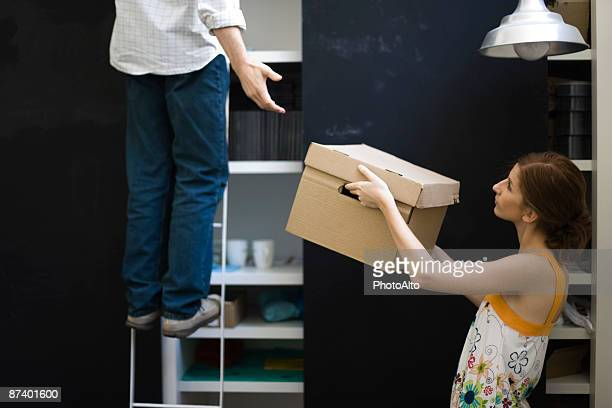 Woman handing box to man standing on ladder