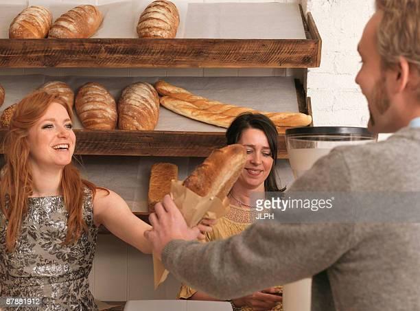 Woman handing bread to customer