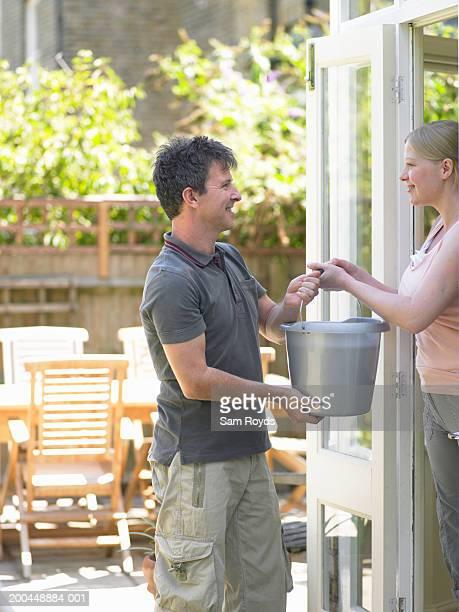Woman handing bucket to man standing in garden by back door