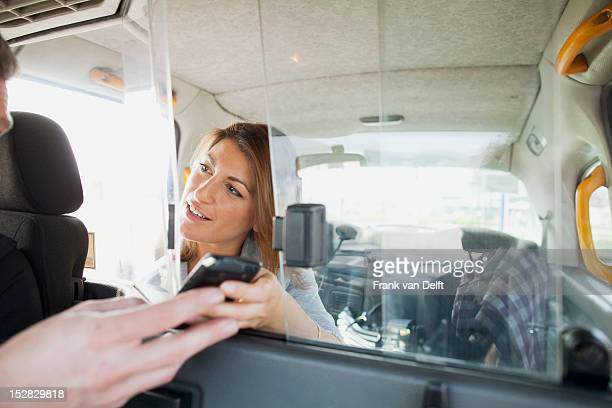Woman handing cell phone to taxi driver