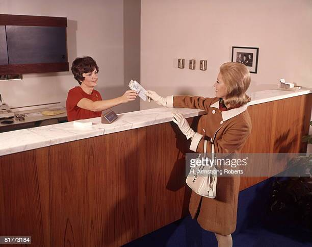 woman handing deposit to bank teller banking women. - 1960 stock pictures, royalty-free photos & images