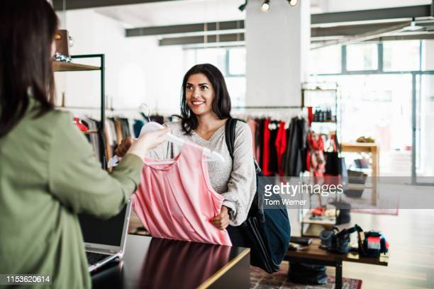 woman handing dress to clothing store cashier - clothing stock pictures, royalty-free photos & images