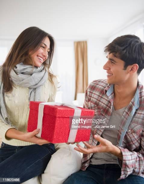 Woman handing husband Christmas gift