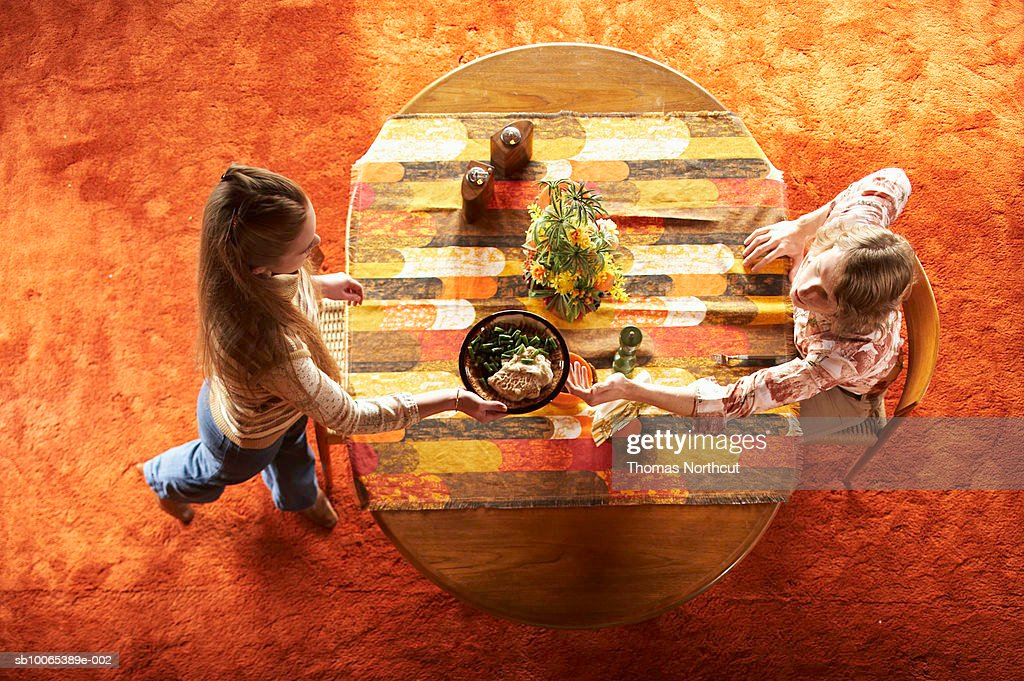 Woman handing man bowl over table, elevated view : Foto stock
