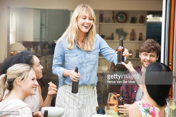 Woman handing out beers to friends sitting in garden.