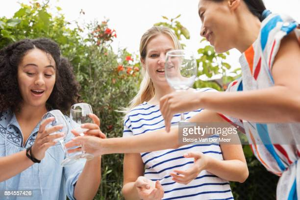 Woman handing out wineglasses to her friends, preparing table for dinner party.