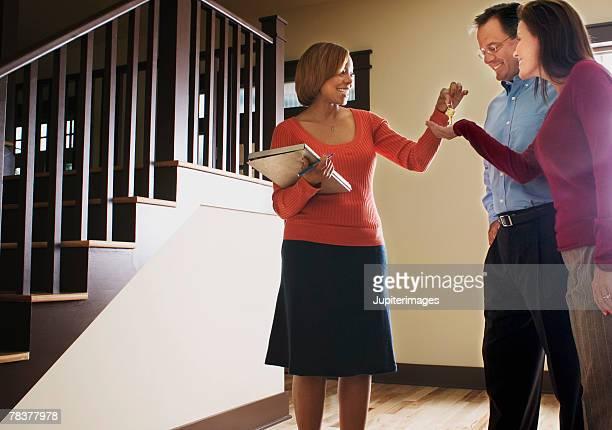 Woman handing over house keys to couple