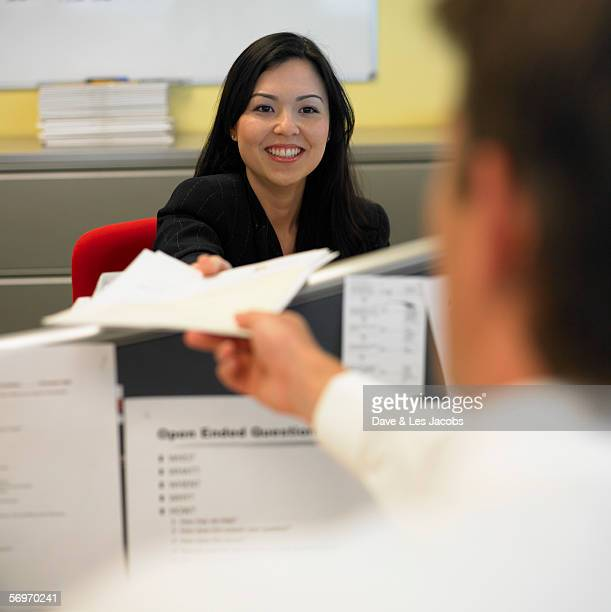 Woman handing papers to man in office