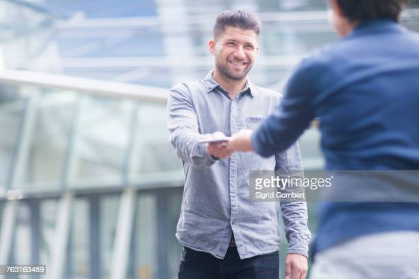 woman handing smiling young man digital tablet - geben stock-fotos und bilder