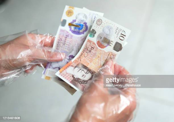 Woman handles banknotes while wearing protective gloves as the UK adjusts to life under the Coronavirus pandemic on March 19, 2020 in Manchester,...