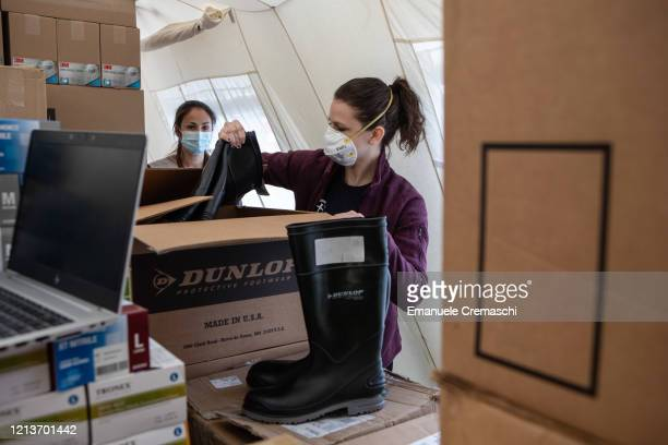 A woman handles protective footwear inside a tent stocked with medical supplies at a Samaritan's Purse Emergency Field Hospital on March 20 2020 in...